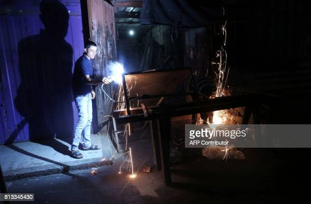 Palestinian man works at a metal workshop during the few hours of electricity supply the residents of the Gaza Strip receive per day on July 11 at...