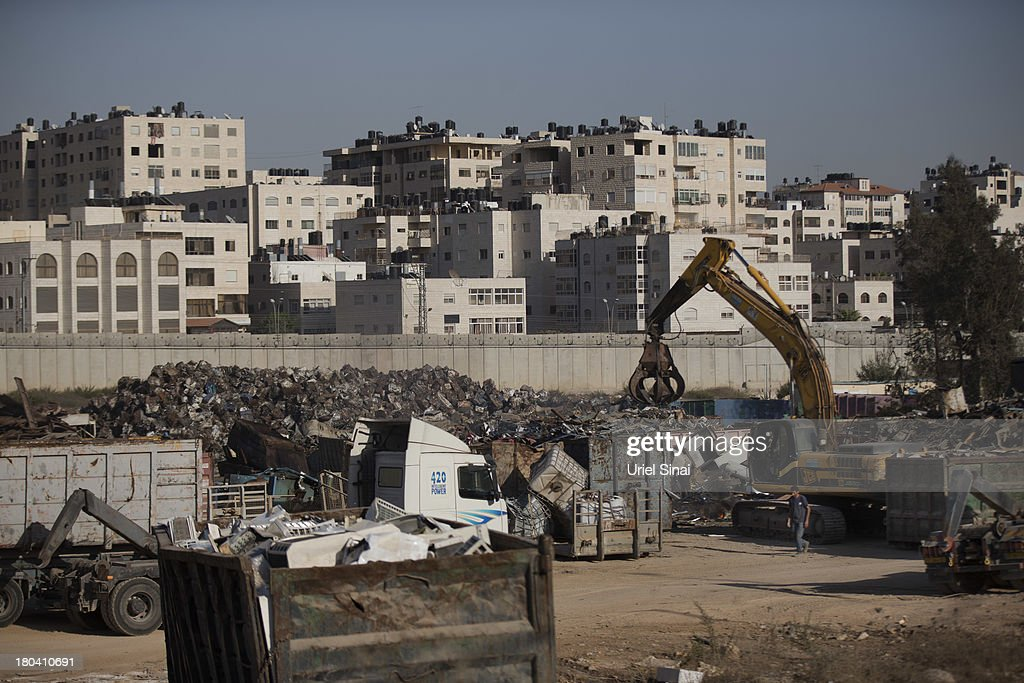 A Palestinian man works in a junkyard near the Israeli West Bank barrier on the outskirts of Jerusalem on September 12, 2013 in Aram, West Bank. The twenty-year anniversary of the Oslo Accord, which was to set up a framework for peace between Israel and Palestine, will be marked on September 13.