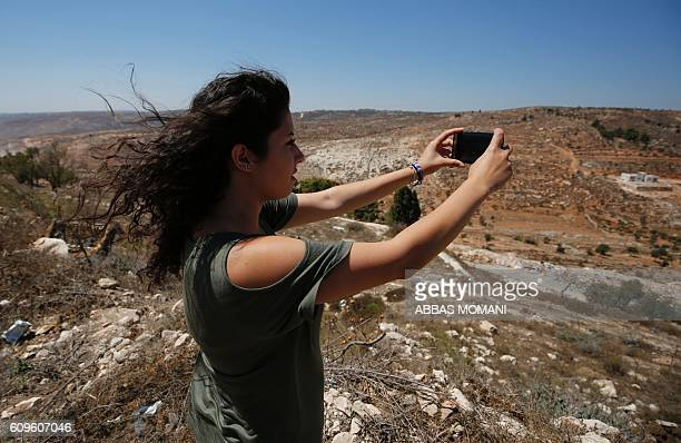 Palestinian Mariane Maadi takes a picture on September 11 as she stands on a hill in the West Bank Christian village of Taybeh overlooking land her...