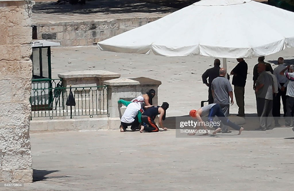 Palestinian masked protesters run for cover as Israeli policemen shoot rubber bullets towards them at Jerusalem's Al-Aqsa mosque during clashes between Israeli police and Muslims protesting Jewish visits to the site on the Muslim holy month of Ramadan, on June 27, 2016. Islamic officials said that trouble began when Israel allowed israeli settlers into the compound in breach of a tradition which only allows worshippers to enter during the last 10 days of Ramadan, which are now in progress. / AFP / THOMAS