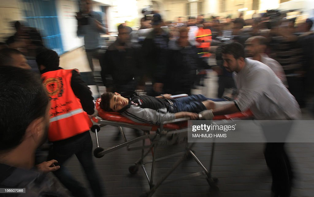 Palestinian medical workers wheel a wounded boy into al-Shifa hospital in Gaza City, on November 16, 2012 . Gaza militants targeted Tel Aviv on Friday with another rocket, defying Israeli warnings of a possible ground assault to follow its aerial bombardment of the Hamas-run strip. AFP PHOTO/MAHMUD HAMS