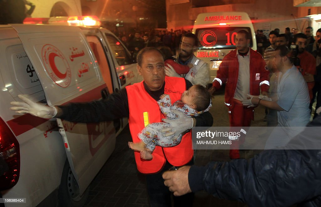 Palestinian medics carry a wounded baby into the al-shifa hospital in Gaza City following an Israeli air strike on November 14, 2012. An Israeli strike that killed Hamas's top commander in Gaza is only 'the beginning' of an operation to target militant groups in the strip, a military spokeswoman said.