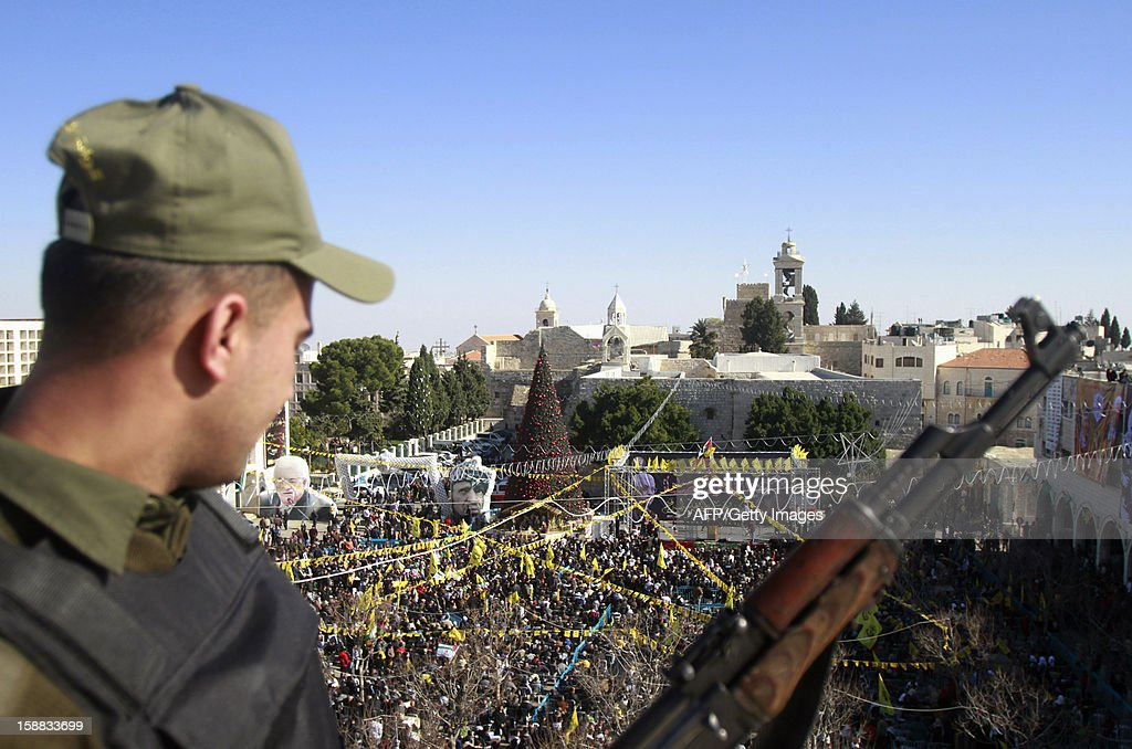 A Palestinian member of security forces stands guard as supporters of Palestinian leader Mahmud Abbas and the Fatah movement gather in front of the Church of the Nativity in the West Bank city of Bethlehem, on December 31, 2012, during celebrations marking the 48th anniversary of the movement's founding.