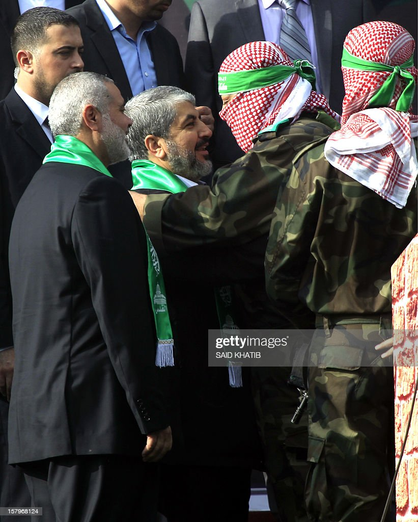 A Palestinian member of the Ezzedine al-Qassam brigades, the armed wing of Hamas, hugs Hamas chief Khaled Meshaal (C) as Hamas prime minister in the Gaza Strip Ismail Haniya (L) looks on during a rally to mark the 25th anniversary of the founding of the Islamist movement, in Gaza City on December 8, 2012. Meshaal made his first visit to Gaza, timed to coincide with the 25th anniversary of the Islamist movement's founding. AFP PHOTO/ SAID KHATIB
