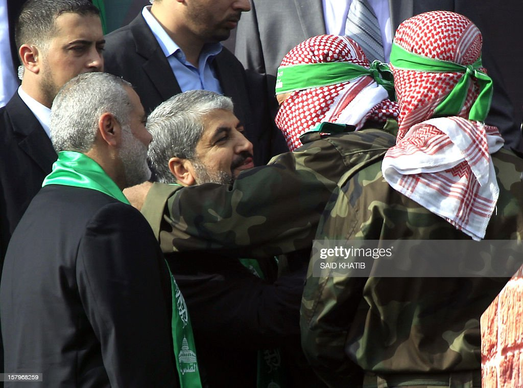 A Palestinian member of the Ezzedine al-Qassam brigades, the armed wing of Hamas, hugs Hamas chief Khaled Meshaal (C) as Hamas prime minister in the Gaza Strip Ismail Haniya (L) looks on during a rally to mark the 25th anniversary of the founding of the Islamist movement, in Gaza City on December 8, 2012. Meshaal made his first visit to Gaza, timed to coincide with the 25th anniversary of the Islamist movement's founding.