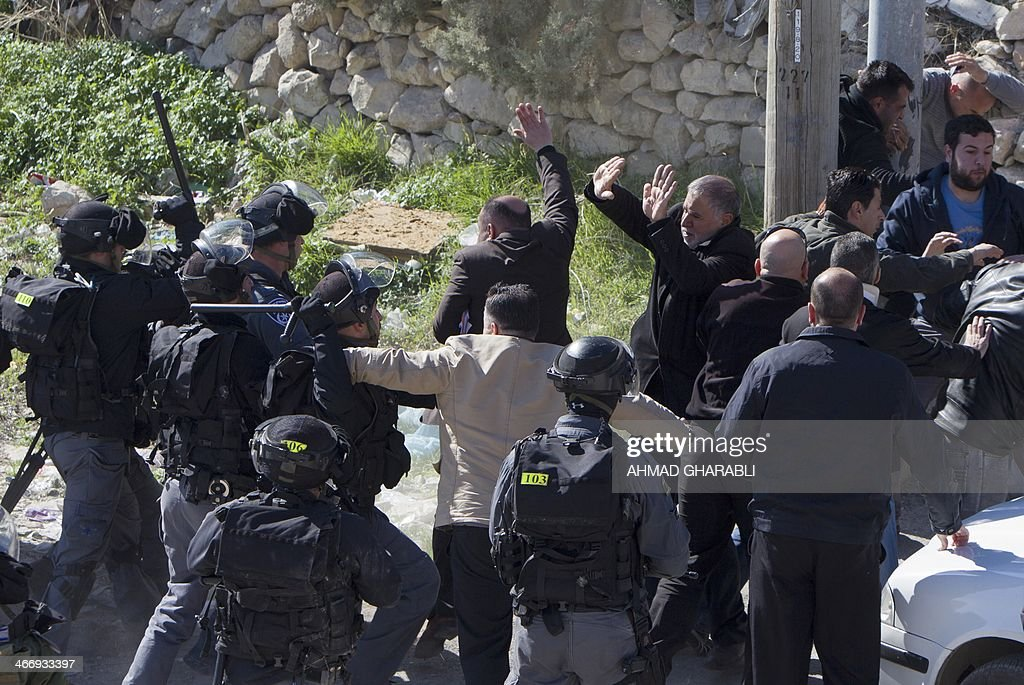 Palestinian members of the Beshr family scuffle with Israeli security forces as Israeli municipality workers (unseen) demolish their house that the authorities said was built without municipal permission, on February 5, 2014 in the Arab east Jerusalem neighborhood of Jabel Mukaber. Israel pushed forward with plans for more than 550 new homes in three settlement neighbourhoods of annexed east Jerusalem, the city council said.