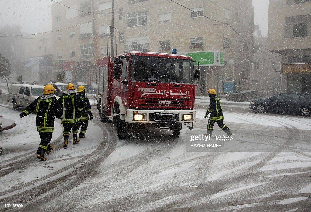Palestinian members of the civil defence patrol the streets as snow falls over the village of Halhoul, near the West Bank town of Hebron, on January 9, 2013. Extreme weather, including torrential rains and heavy winds, killed four people in Israel and the Palestinian territories on January 8, as widespread flooding swept the Middle East. AFP PHOTO / HAZEM BADER