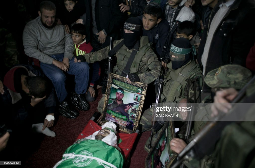 Palestinian members of the Ezzedine al-Qassam Brigades, the armed wing of the Hamas movement pray over the body of their comrade Marwan Maarouf, 27, during his funeral in Khan Yunis in the southern Gaza Strip, on February 9, 2016. Maarouf was killed when a tunnel collapsed in the Gaza Strip, Hamas said, in the fourth such incident over the past few weeks. The death brings to 11 the number of Gazans killed in four separate collapses since January 26, and comes with Israeli concern building over the reconstruction of tunnels it says could be used for attacks. / AFP / SAID KHATIB