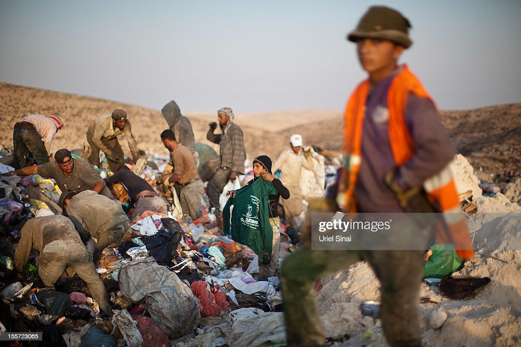 Palestinian men and children sift through a garbage dump on November 7, 2012 south of Hebron, West Bank. About 40 Palestinain men and children work at the West Bank garbage dump looking for clothing, metal and wood discarded, in large part, from the Jewish settelment in the region.