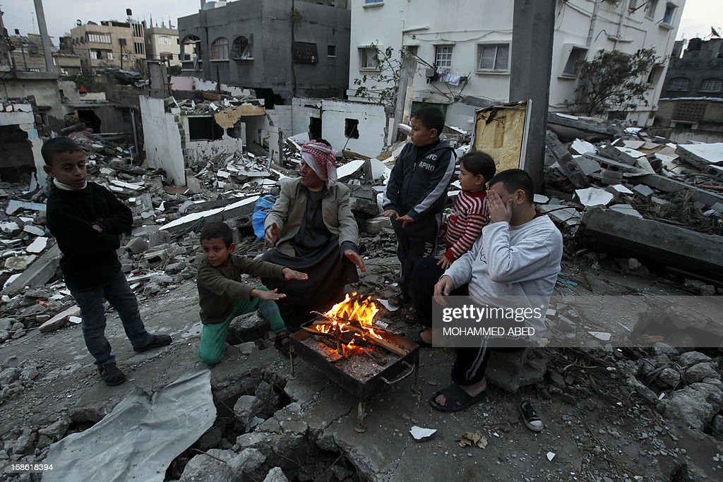 Palestinian men and children warm themselves by a fire next to houses which were destroyed during November's eight-day confrontation between Israel and Gaza militants, on December 21, 2012 in Beit Lahia, northern Gaza Strip. The eight-day confrontation claimed the lives of 177 Palestinians, mostly civilians, and six Israelis, medical sources on both sides said. AFP PHOTO/MOHAMMED ABED