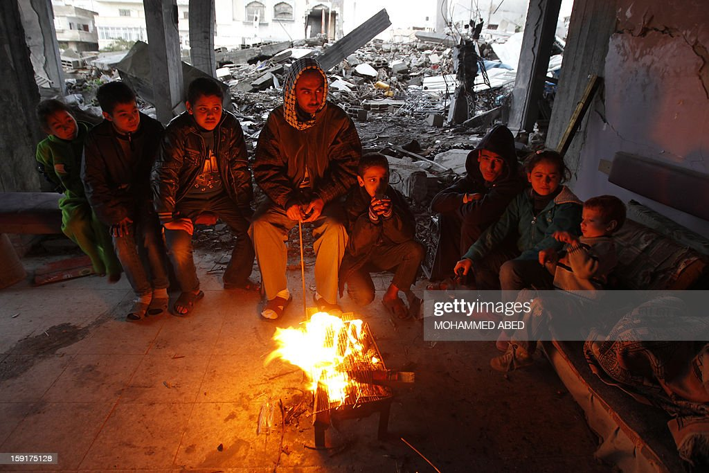 Palestinian men and children warm themselves by a fire next to houses which were destroyed during November's eight-day confrontation between Israel and Gaza militant on January 9, 2013 in Gaza City. A storm has hit the eastern Mediterranean coast and heavy rains with flooding are forecast in Israel and the Palestinian territories for the next couple of days, with a good chance of snow falling in the higher elevations. AFP PHOTO/MOHAMMED ABED