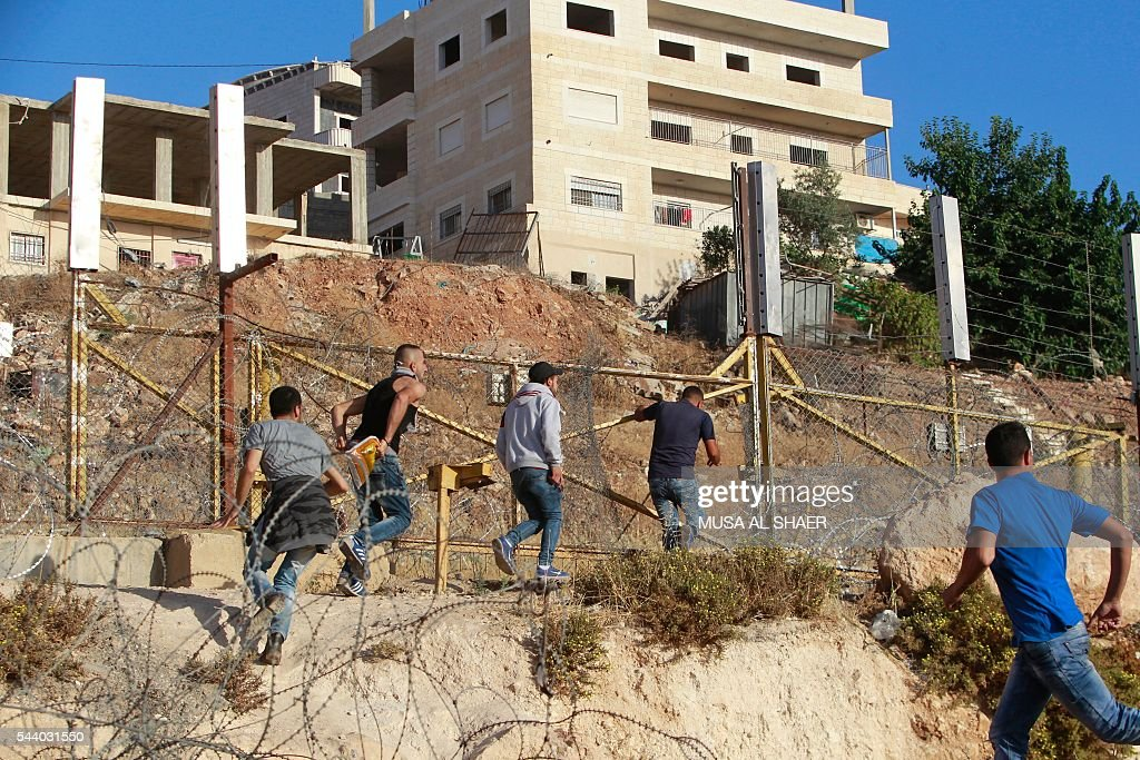 Palestinian men attempt to cross through a gap in the barbed-wire gate part of the controversial Israeli separation fence between the West Bank town of Bethlehem and Jerusalem, after Israeli police prevented them from crossing to pray at Al-Aqsa Mosque compound on the fourth and the last Friday of the Muslim holy month of Ramadan, on July 1, 2016. Israeli authorities announced on June 28 they were closing Jerusalem's flashpoint Al-Aqsa mosque compound to non-Muslim visitors until the end of the Muslim holy month of Ramadan after a series of clashes between worshippers and Israeli police. Clashes have been taking place every morning since the beginning of the week over Jewish visits to the site, with youths throwing stones and security forces firing tear gas and sponge-tipped bullets. / AFP / MUSA