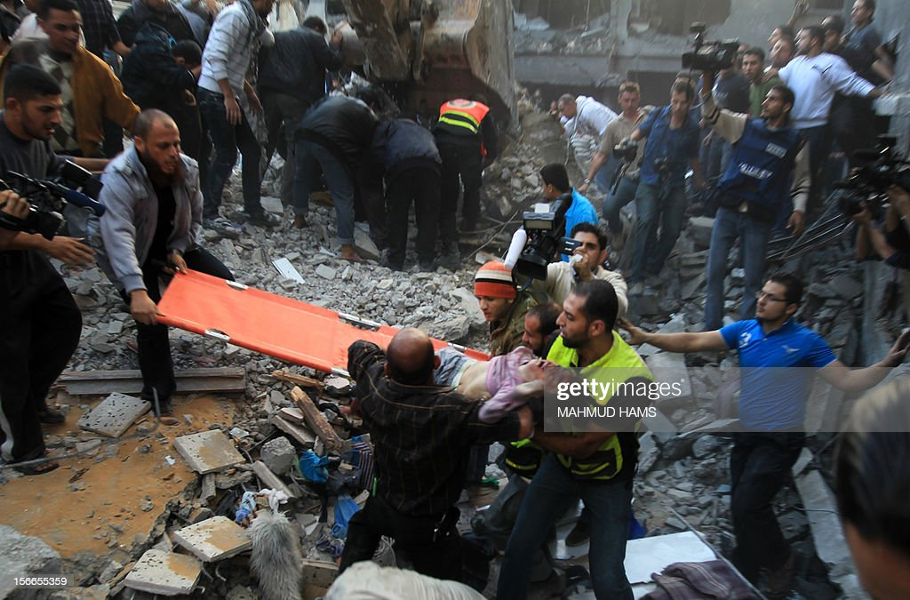 Palestinian men carry the dead body of a child from the al-Dallu family out from the rubble after an Israeli missile struck a family home killing at least seven members of the same family in Gaza City on November 18, 2012.