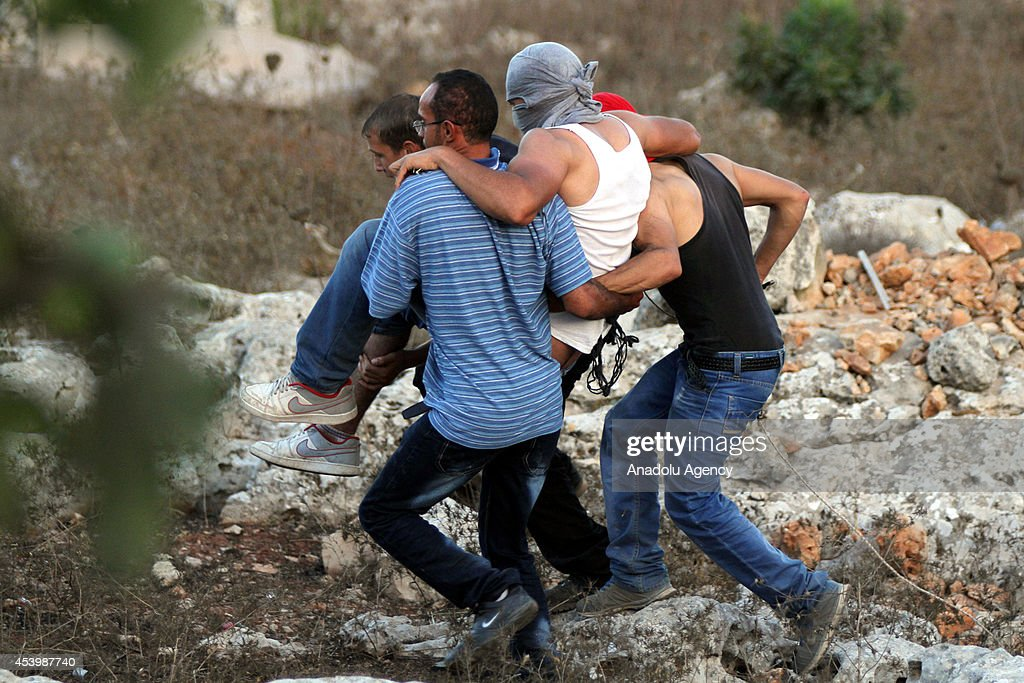 Palestinian men carry their injured friend during the Israeli soldiers' intervention to disperse protestors gathering in Silvad village in Ramallah, West Bank on August 22, 2014, against Israeli attacks on Gaza.