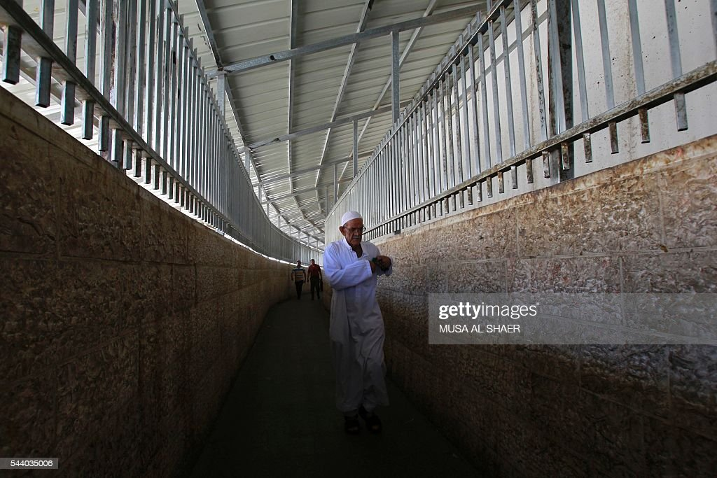 Palestinian men cross an Israeli checkpoint between the West Bank town of Bethlehem and Jerusalem, as they head to Jerusalem's Al-Aqsa Mosque compound on the forth and last Friday of the Muslim holy month of Ramadan on July 1 , 2016. Israeli authorities announced on June 28 they were closing Jerusalem's flashpoint Al-Aqsa mosque compound to non-Muslim visitors until the end of the Muslim holy month of Ramadan after a series of clashes between worshippers and Israeli police. Clashes have been taking place every morning since the beginning of the week over Jewish visits to the site, with youths throwing stones and security forces firing tear gas and sponge-tipped bullets. / AFP / MUSA