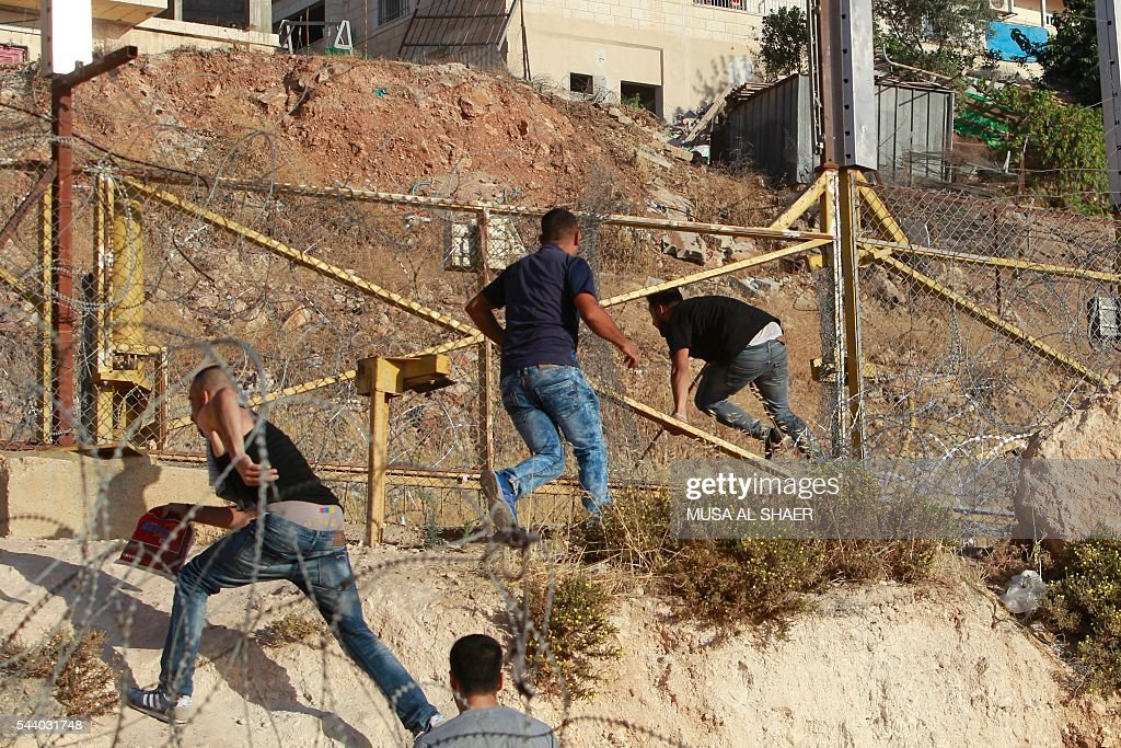 Palestinian men cross through a gap in the barbed-wire gate part of the controversial Israeli separation fence between the West Bank town of Bethlehem and Jerusalem, in an attempt to reach the Al-Aqsa Mosque compound in Jerusalem, after Israeli police prevented them from crossing to pray on the fourth and last Friday of the Muslim holy month of Ramadan, on July 1, 2016. Israeli authorities announced on June 28 they were closing Jerusalem's flashpoint Al-Aqsa mosque compound to non-Muslim visitors until the end of the Muslim holy month of Ramadan after a series of clashes between worshippers and Israeli police. Clashes have been taking place every morning since the beginning of the week over Jewish visits to the site, with youths throwing stones and security forces firing tear gas and sponge-tipped bullets. / AFP / MUSA