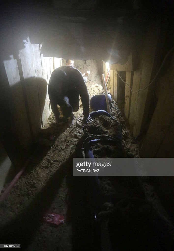 Palestinian men dig a hole on the Egyptian side of the border as they repair a bombed smuggling tunnel linking the Gaza Strip to Egypt, in Rafah, on November 29, 2012. Israeli airforce jets bombed most of the smuggling tunnels in the southern Gaza Strip during its war against the Islamist movement Hamas, which rules the coastal Palestinian territory, between 14 and 21 of November 2012.