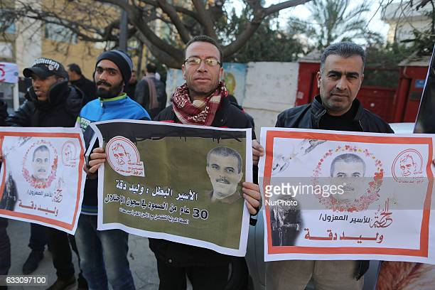 Palestinian men hold banners during a demonstration in support of her relatives held in Israeli prisons in front of the International Red Cross and...