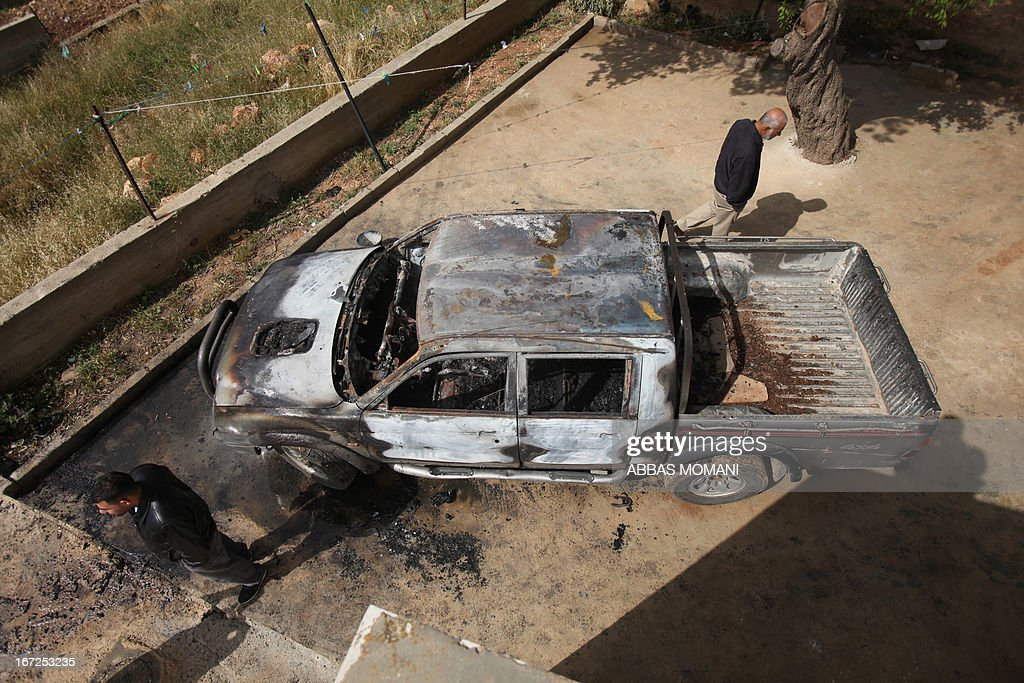 Palestinian men inspect a burnt vehicle that according to them was set on fire by Israeli settlers on April 23, 2013 in the village of Deir Jarir East of the West Bank city of Ramallah. The Israeli police opened an investigation after ten Palestinian vehicles were set ablaze in a West Bank village near Ramallah, an act attributed by residents to Israeli settlers. AFP PHOTO/ ABBAS MOMANI