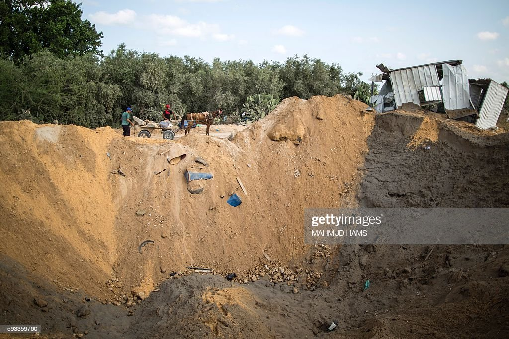 Palestinian men load stones on a cart next to a crater on August 22 2016 in Beit Lahia in the northern Gaza Strip following an Israeli airstrike the...