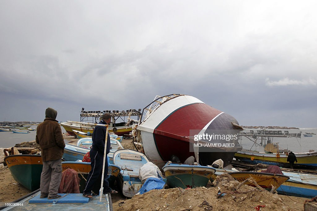 Palestinian men look at damaged boats after a storm on January 10, 2013 in Gaza City. In Gaza, cold weather and heavy rain flooded several of the tunnels running between the territory and Egypt as in the West Bank city of Ramallah, children and adults, including some policeman stopped their cruiser for an impromptu snowball fight.