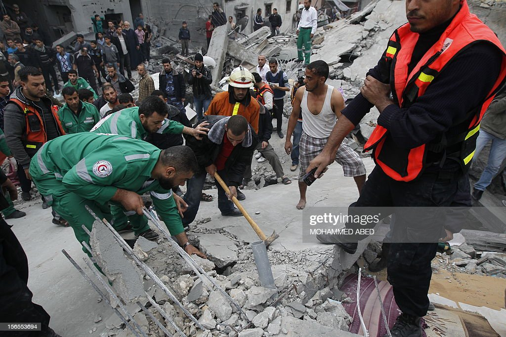 Palestinian men look for injured people amongst the rubble following an Israeli air raid on a house in Beit Lahia, the northern Gaza Strip on November 17, 2012. Israeli air strikes hit the cabinet headquarters of Gaza's Hamas government, the group said early on November 17, with eyewitnesses reporting extensive damage to the building.