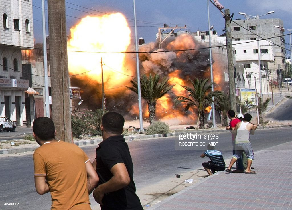 Palestinian men look on as a bomb from an Israeli air strike hits a house in Gaza City on August 23 2014 Israel kept up the pressure on Hamas in Gaza...
