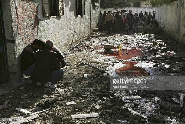 Palestinian men mourn next to water stained with blood after Israeli tanks fired on homes in Beit Hanoun November 8 2006 in Beit Hanoun in the...