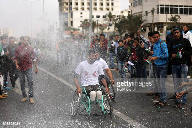 Palestinian men on their wheelchairs compete in a marathon organised for Palestinians who have been wounded by wars on November 29 2016 in Gaza City...
