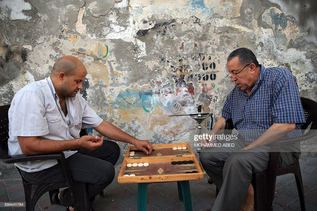 Palestinian men play backgammon in Gaza City on May 26, 2016. / AFP / MOHAMMED