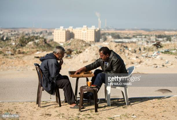 TOPSHOT Palestinian men play backgammon next their home in Beit Lahia in the northern Gaza Strip on February 6 2017 Israel struck a number of Hamas...