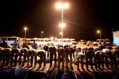 Palestinian men pray as they wait to be collected by their Israeli employers after crossing from the West Bank town of Qalqilya to work in the Jewish...