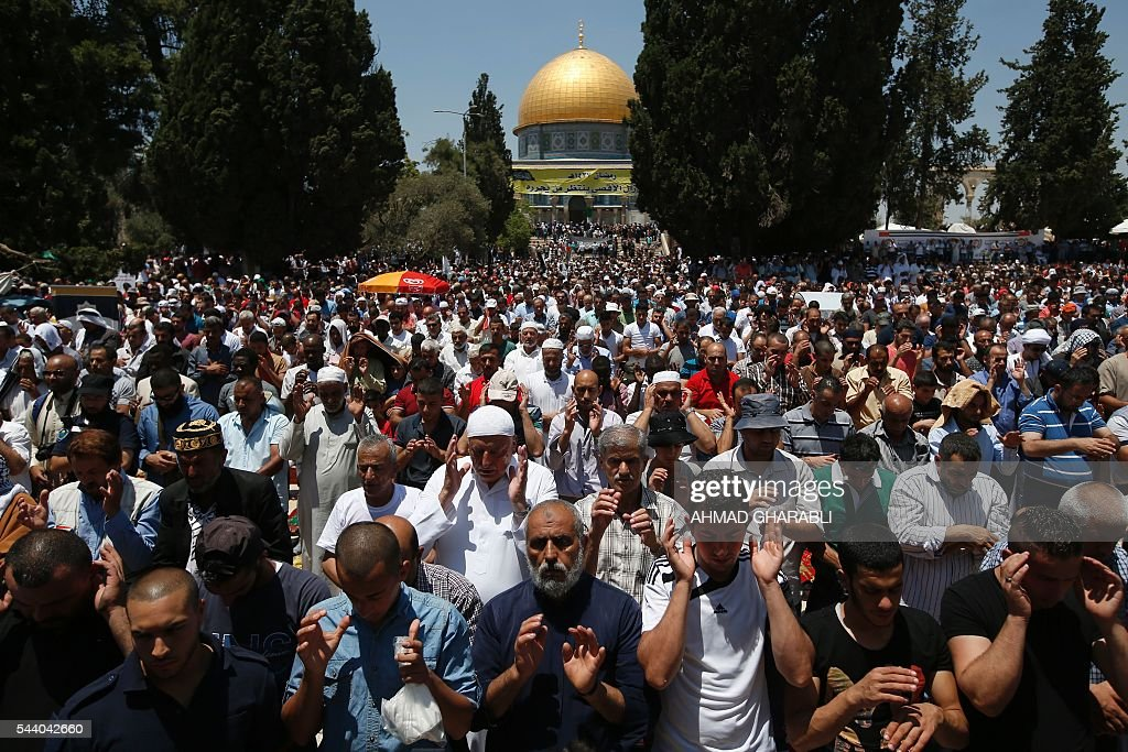 Palestinian men pray outside the Dome of the Rock in Jerusalem's Al-Aqsa mosque compound during the last Friday prayers of the holy Muslim fasting month of Ramadan on July 1, 2016. / AFP / AHMAD