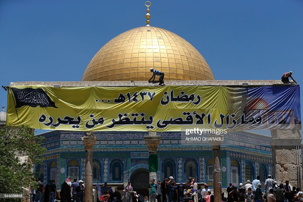 Palestinian men put up a banner on the front side of the Dome of the Rock in Jerusalem's Al-Aqsa mosque compound during the last Friday prayers of the holy Muslim fasting month of Ramadan, on July 1, 2016. The writing in Arabic reads: 'Ramadan 1437 A.H... and still the Al-Aqsa waits for someone to liberate it'. / AFP / AHMAD