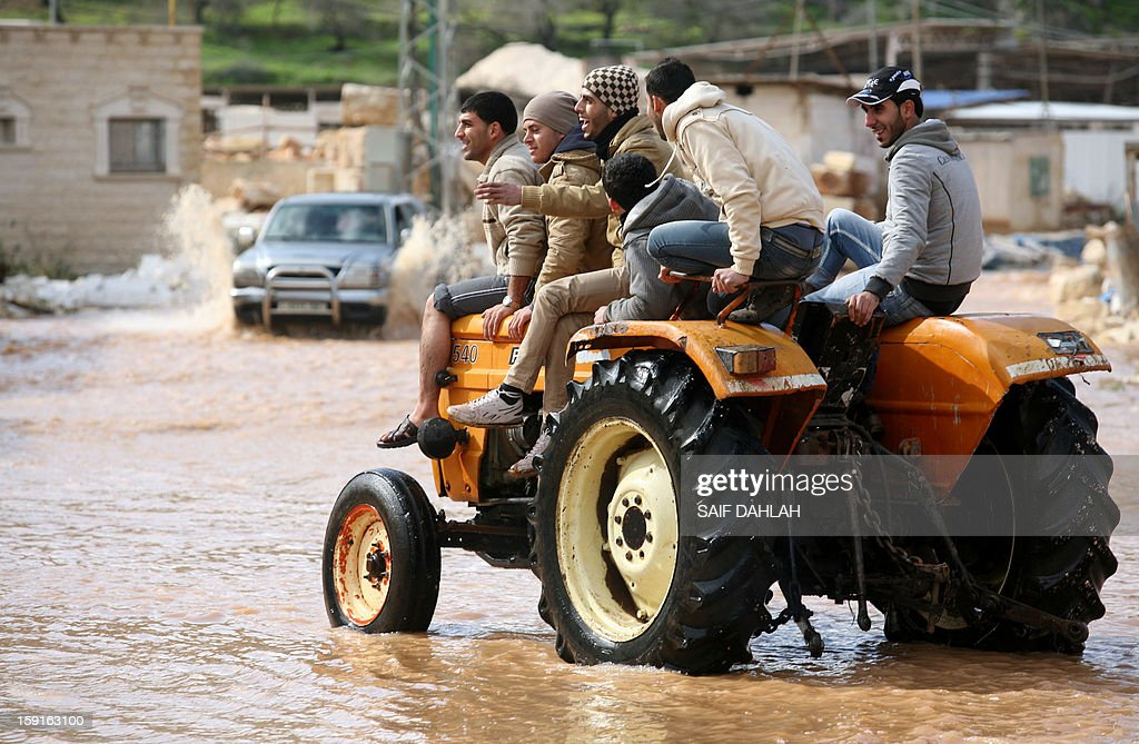 Palestinian men ride on a tractor through flood waters in the village of Qabatiya, in the Israeli occupied West Bank near the northern city of Jenin, on January 9, 2013, as rain and snow engulfs the Levant. AFP PHOTO/SAIF DAHLAH