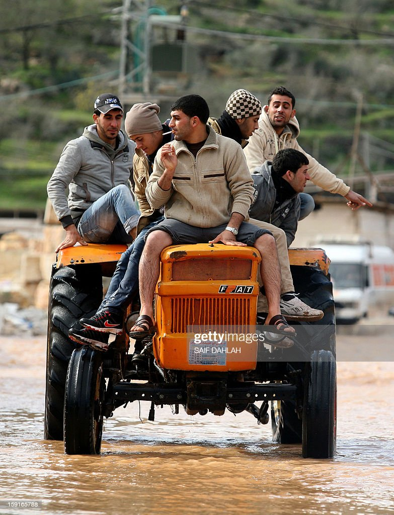 Palestinian men ride on a tractor through flooded waters in the village of Qabatiya, in the Israeli occupied West Bank near the northern city of Jenin, on January 9, 2013, as rain and snow engulfs the Levant.