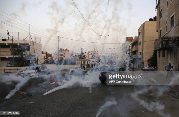 TOPSHOT Palestinian men run for cover from tear gas during clashes between demonstrators and Israeli security forces at the Qalandiya checkpoint...