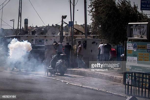 Palestinian men run from a stun grenade after a noon Friday prayer outside Ras Al Amud neighbourhood on October 16 2015 in Jerusalem Israel As...