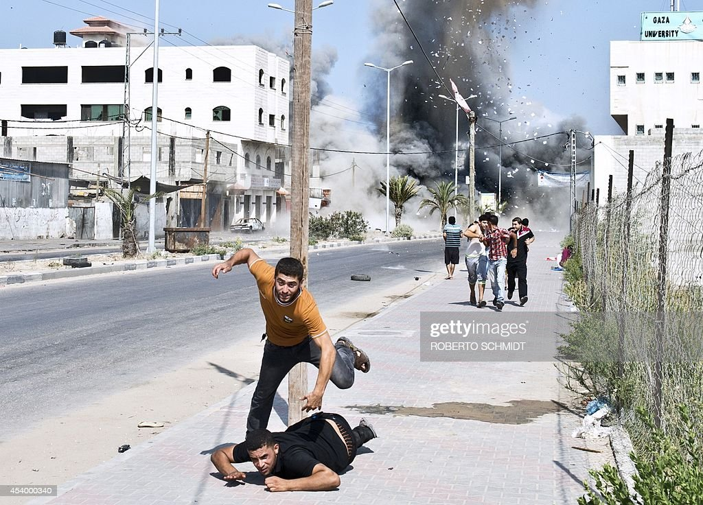 Palestinian men scramble to run away from debris after a bomb from an Israeli air strike hit a house in Gaza City on August 23 2014 Israel kept up...