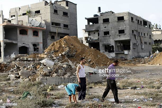 Palestinian men search through the rubble of buildings following an Israeli air strike that killed 18 people of the same family in Gaza City on July...