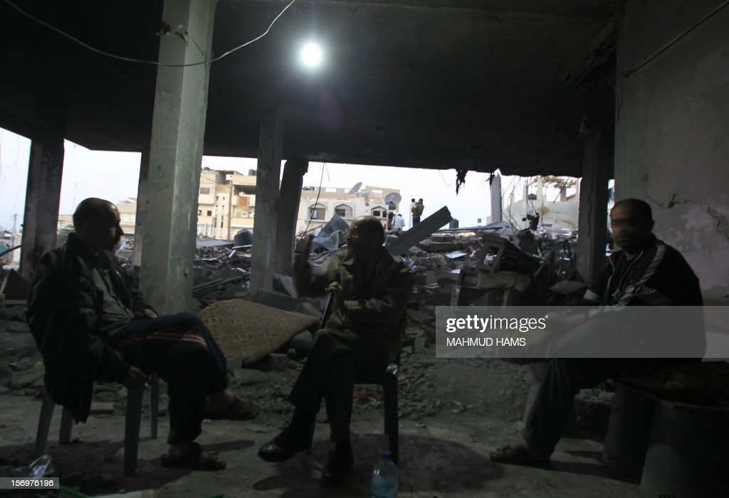 Palestinian men sit talking close to the rubble of a destroyed building in Beit Lahia, in the northern Gaza Strip, on November 26, 2012, following a truce last week between Israel and Hamas that ended eight days of conflict in which 166 Palestinians and six Israelis were killed.