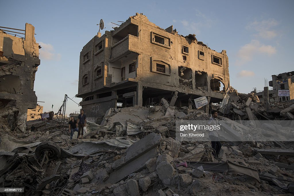 Palestinian men stand amongst the rubble of a destroyed area of housing on August 16 2014 in Gaza City Gaza A fiveday ceasefire between Palestinian...