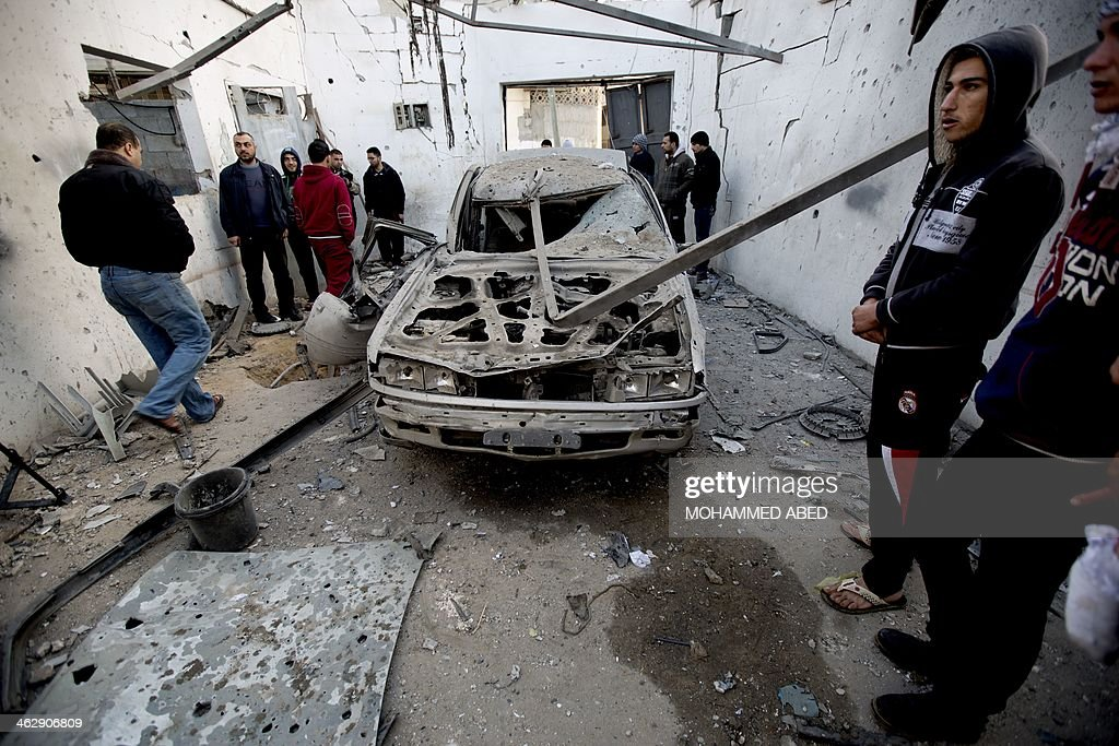 Palestinian men stand around a destroyed car after overnight Israeli air strikes in Gaza City on January 16, 2014. Israeli air strikes in the Gaza Strip against training camps used by the armed wing of the territory's Hamas rulers left four children and a woman wounded, Palestinian medical sources said.