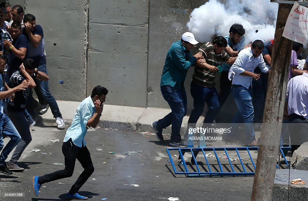 Palestinian men take cover from a stun grenade thrown by Israeli security forces during clashes at the Qalandia checkpoint between Ramallah and Jerusalem on July 1, 2016, as Israeli authorities banned men under 45 from accessing the Al-Aqsa mosque compound for Friday prayers. The Palestinian health ministry said that a middle-aged man had died from tear gas fired by Israeli forces during a clash at the Qalandia crossing. Israeli police said in a statement that three members of the security forces were injured by stones but it reported no Palestinian casualties. / AFP / ABBAS