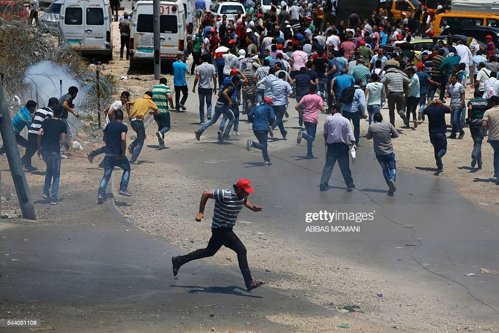 Palestinian men take cover from tear gas fired by Israeli security forces during clashes at the Qalandia checkpoint between Ramallah and Jerusalem on July 1, 2016, as Israeli authorities banned men under 45 from accessing the Al-Aqsa mosque compound for Friday prayers. The Palestinian health ministry said that a middle-aged man had died from tear gas fired by Israeli forces during a clash at the Qalandia crossing. / AFP / ABBAS