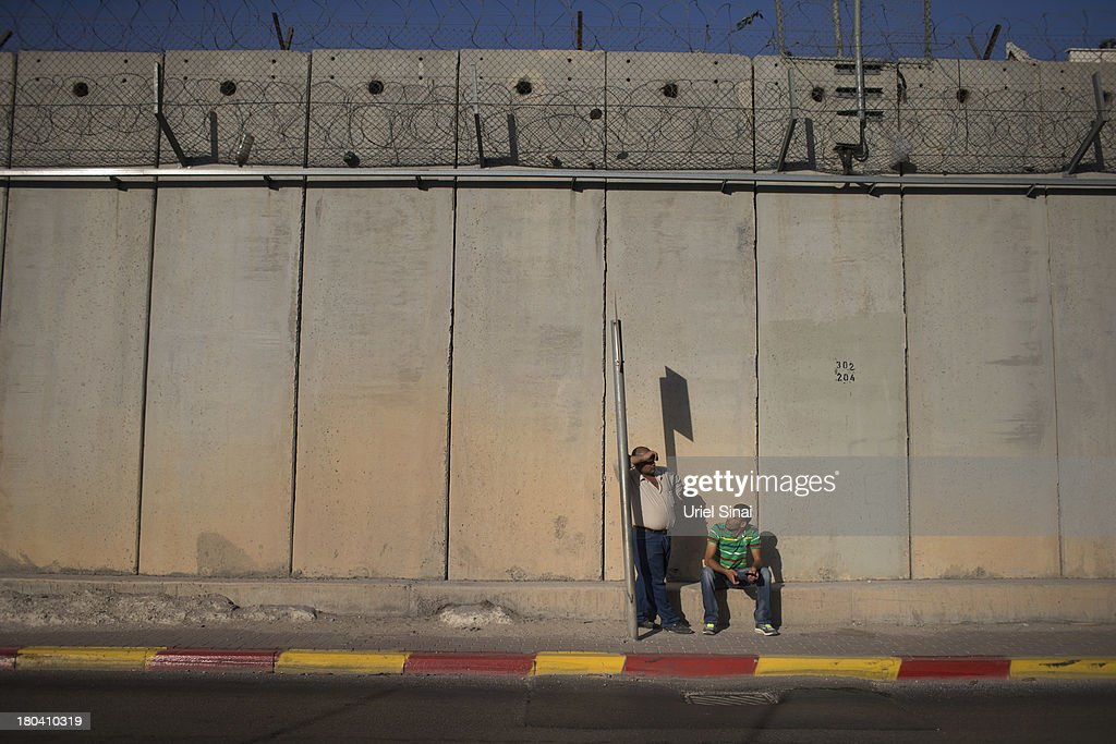 Palestinian men wait for a bus along the Israeli West Bank barrier on the outskirts of Jerusalem on September 12, 2013 in Aram, West Bank. The twenty-year anniversary of the Oslo Accord, which was to set up a framework for peace between Israel and Palestine, will be marked on September 13.
