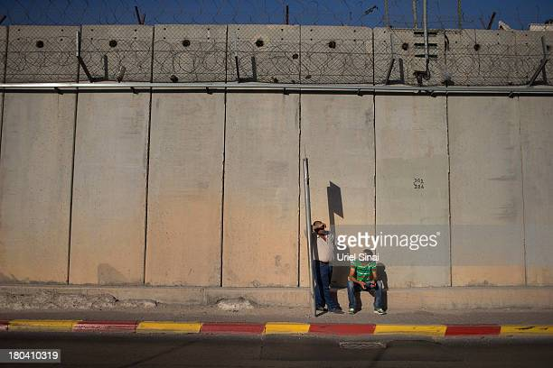 Palestinian men wait for a bus along the Israeli West Bank barrier on the outskirts of Jerusalem on September 12 2013 in Aram West Bank The...