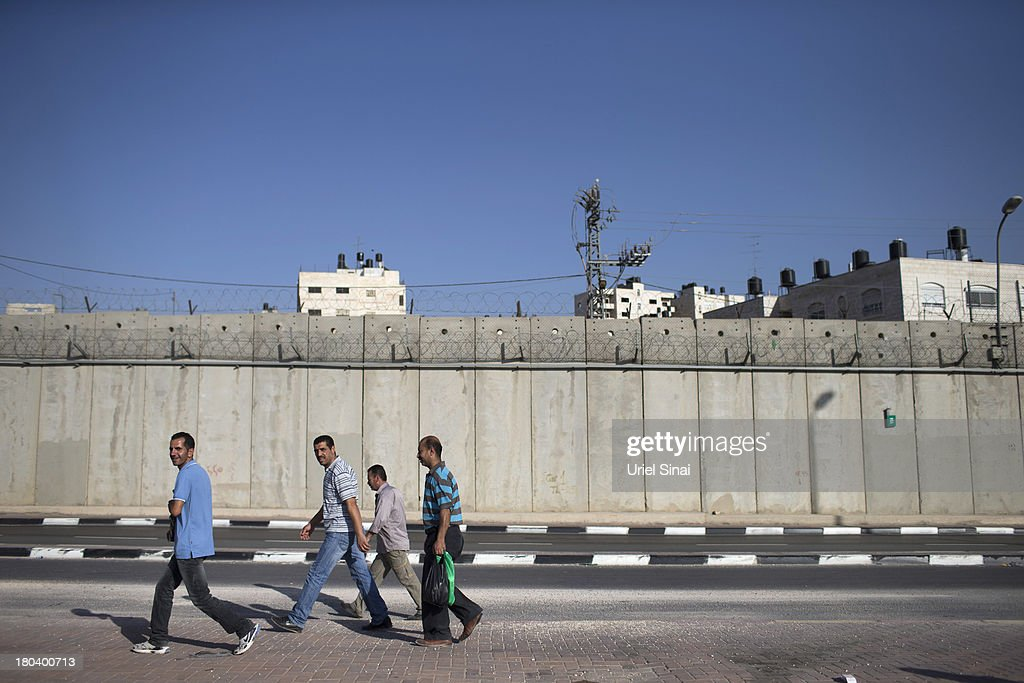 Palestinian men walk along the Israeli West Bank barrier on the outskirts of Jerusalem on September 12, 2013 in Aram, West Bank. The twenty-year anniversary of the Oslo Accord, which was to set up a framework for peace between Israel and Palestine, will be marked on September 13.