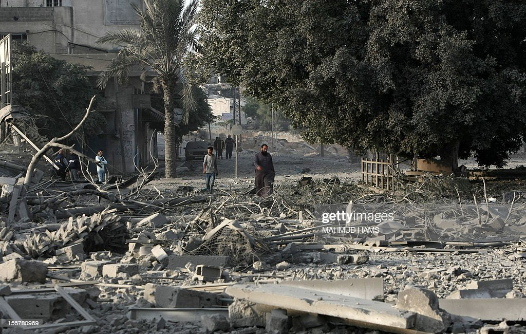 Palestinian men walk amidst debris at the destroyed compound of the internal security ministry in Gaza City after it was targeted by an Israeli air strike overnight on November 21, 2012. Fighting raged on both sides of Gaza's borders Wednesday despite intensified efforts across the region to thrash out a truce to end a week of violence that has cost 136 Palestinian and five Israeli lives. AFP PHOTO/MAHMUD HAMS