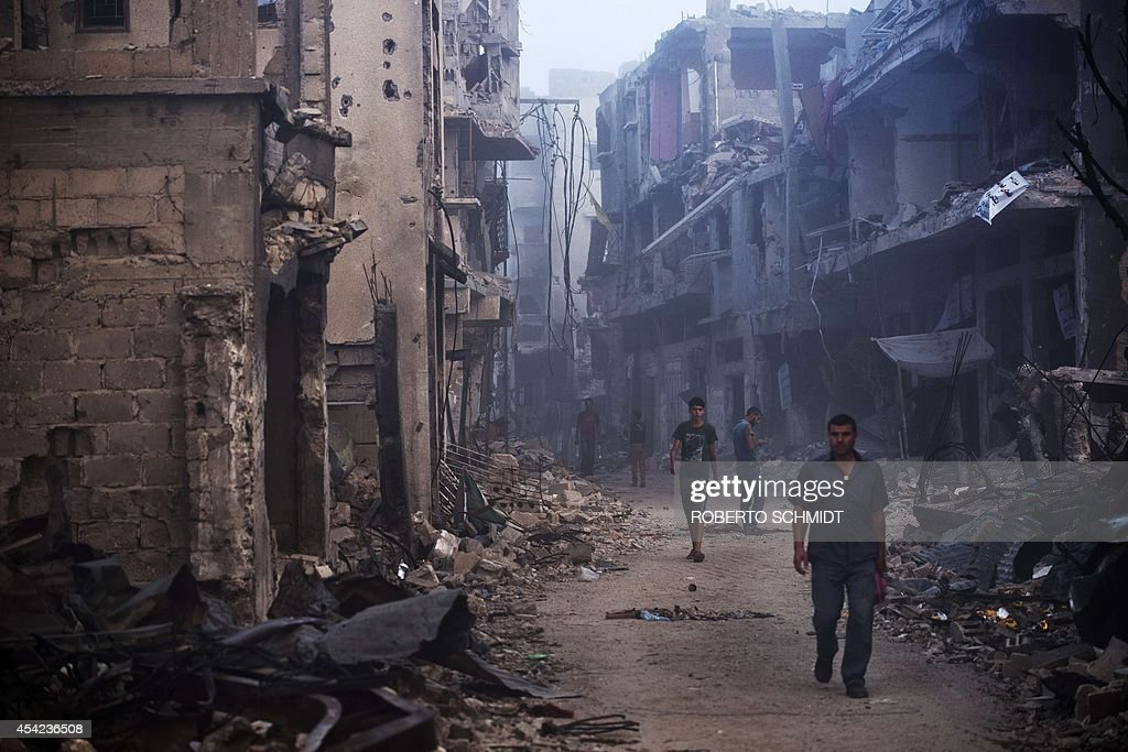 Palestinian men walk in a street on August 27 2014 among houses destroyed in Gaza City's Shejaiya neighbourhood which was one of the hardest hit hit...